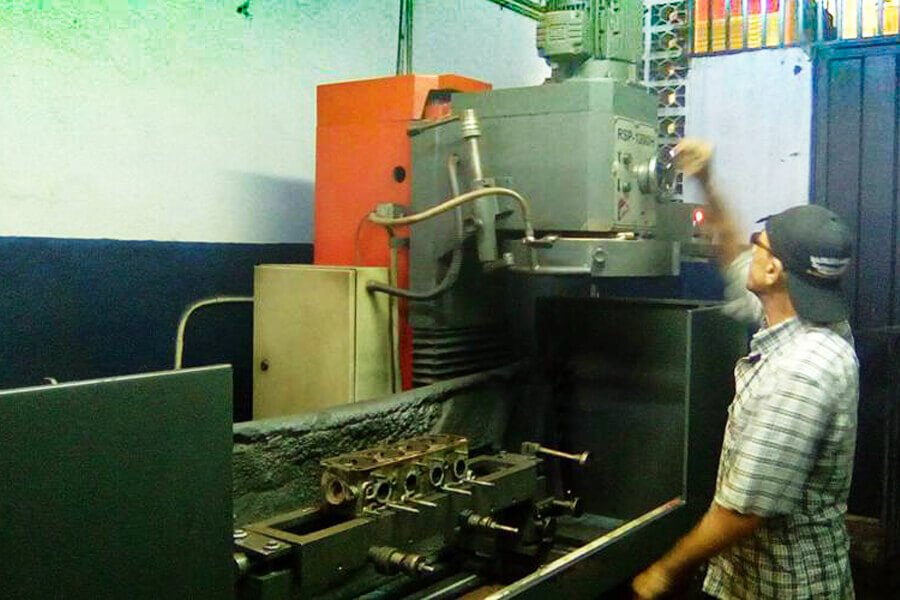 Mr. Jorge Orlando Cadavid while is grinding a cylinder head in his workshop