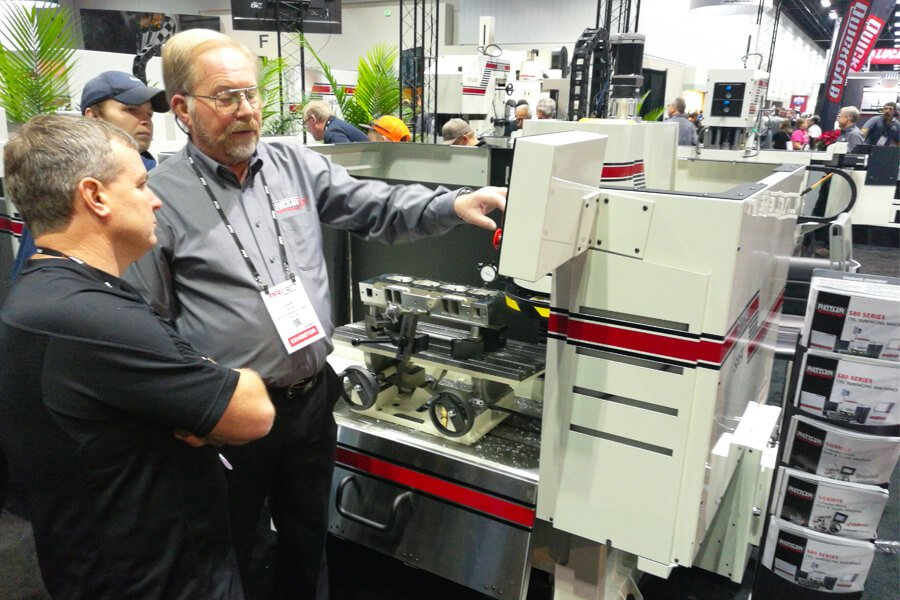 A Rottler technician explains the Rottler S85A to visitors of the PRI Show
