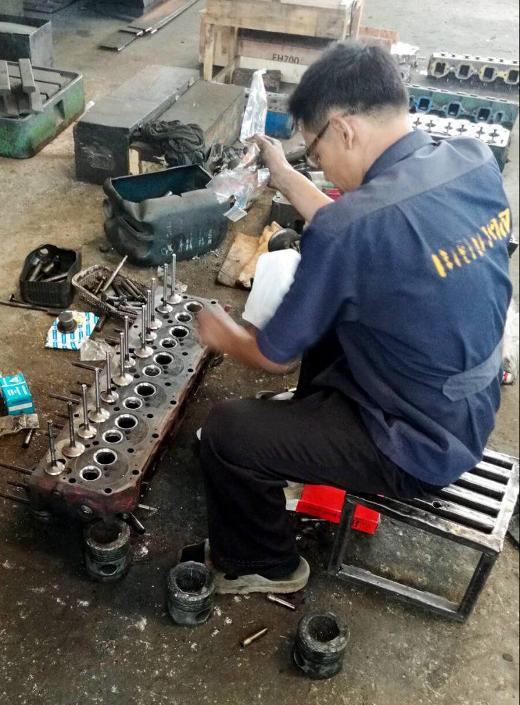 Operador está desmontando válvulas de motor